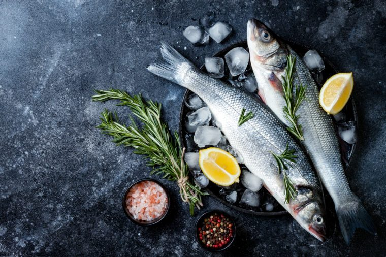 Fresh raw seabass fish on black stone background with spices, herbs, lemon and salt. Culinary seafood background with ingredients for cooking. Top view