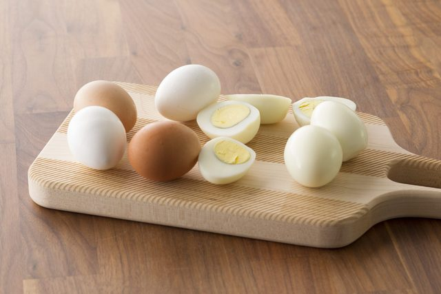 Peeled and halved hard boiled eggs laid out on a cutting board