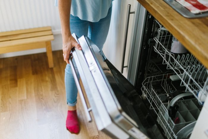 anonymous woman standing in a kitchen opening the dishwasher
