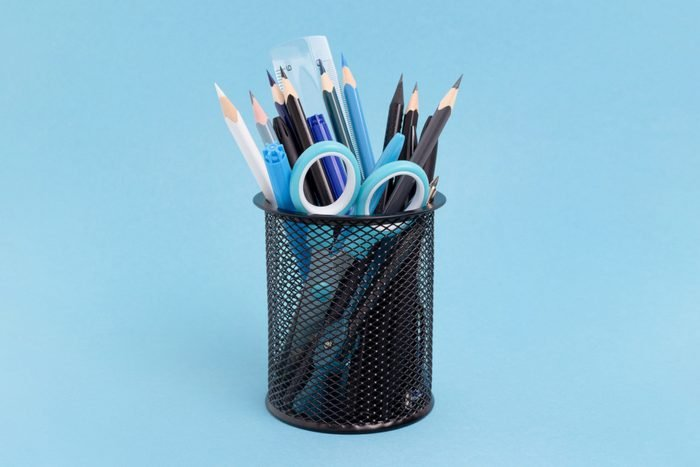 metal pen holder cup with pencils and stationary items on blue background