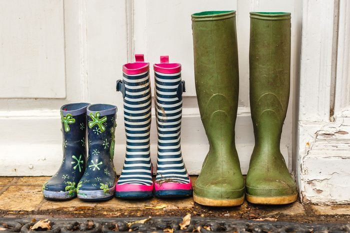 three pairs of dirty rainboots lined up outside a door