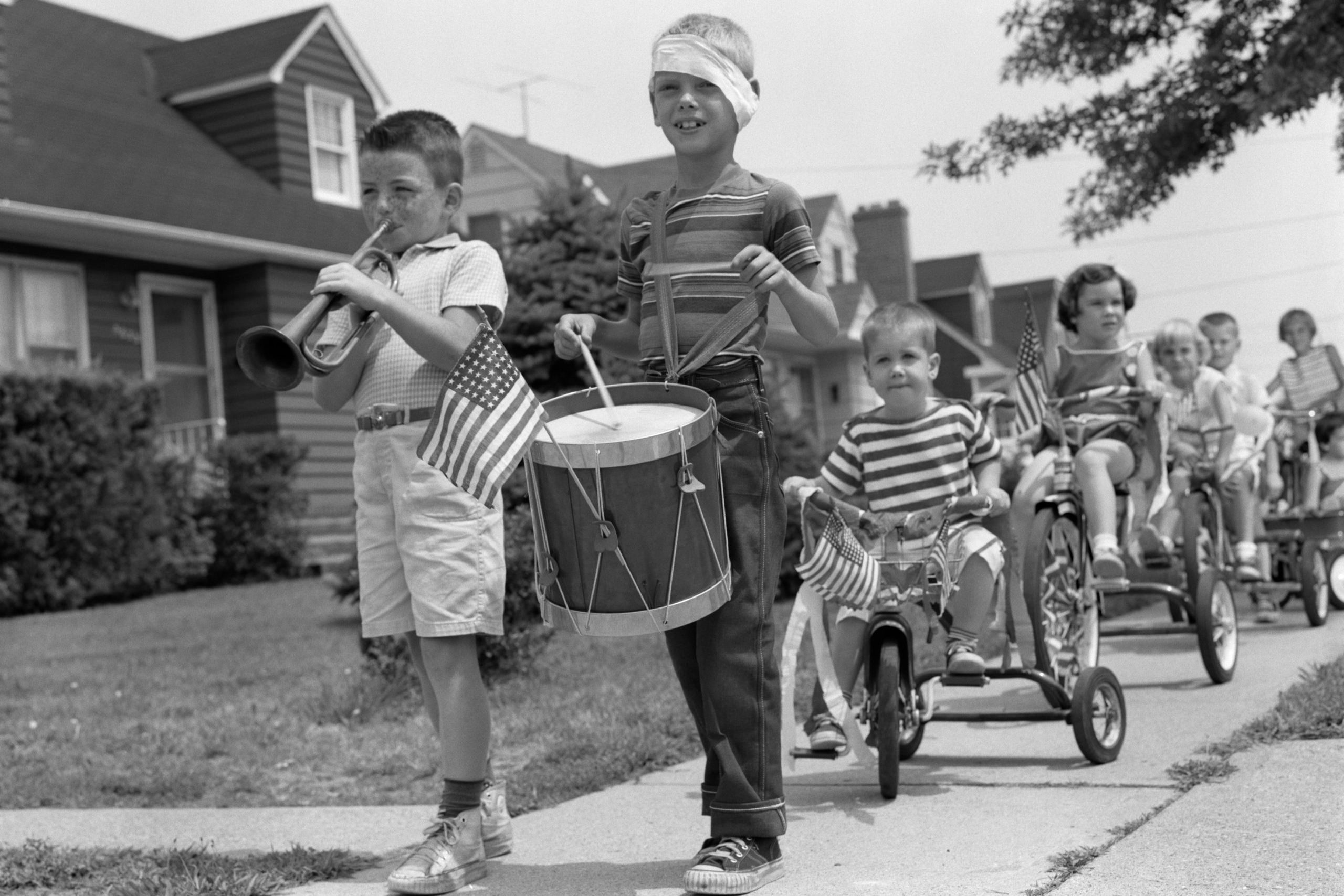 1960s CHILDREN IN FOURTH OF JULY PARADE RIDING TRICYCLES ON SIDEWALK PLAYING DRUM AND TRUMPET MUSIC