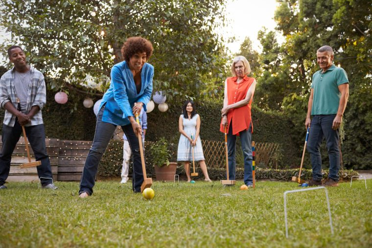 Group Of Mature Friends Playing Croquet In Backyard Together
