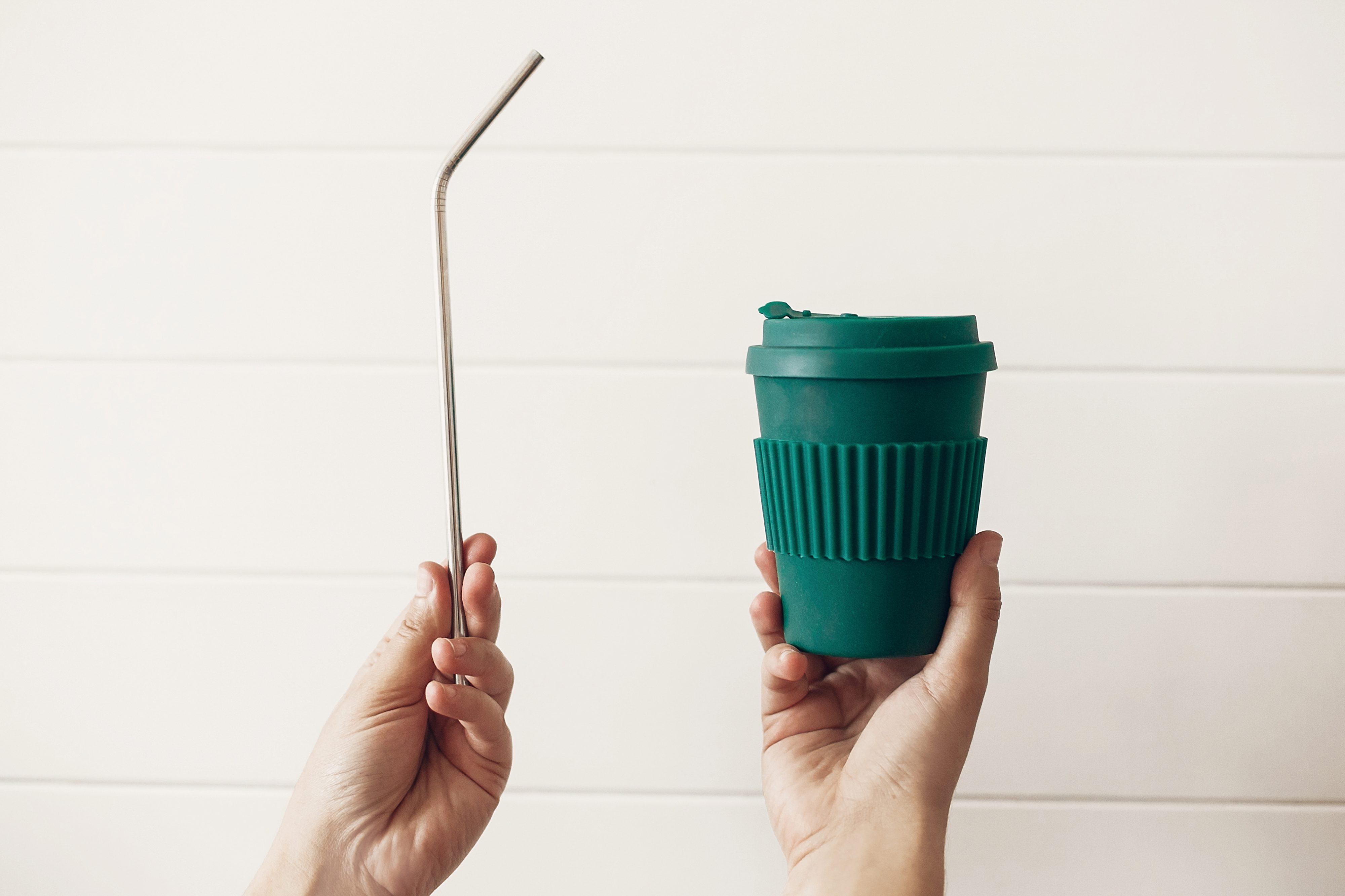 Hands holding stylish reusable eco coffee cup and steel straw on white wooden background. Zero waste. Green Cup from natural bamboo fiber and metallic straw, Ban single use plastic.