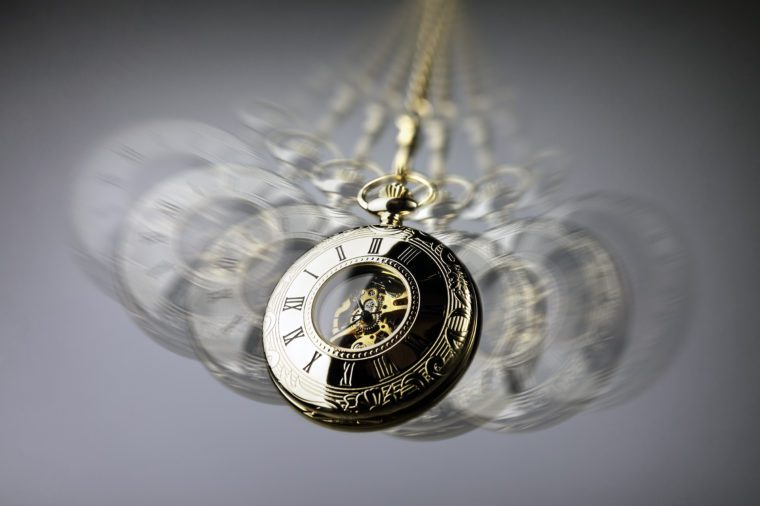 Hypnotism concept, gold pocket watch swinging used in hypnosis treatment