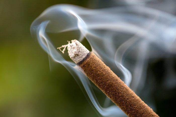 Incense stick burning with smoke, close up, macro. Island Bali, Ubud, Indonesia
