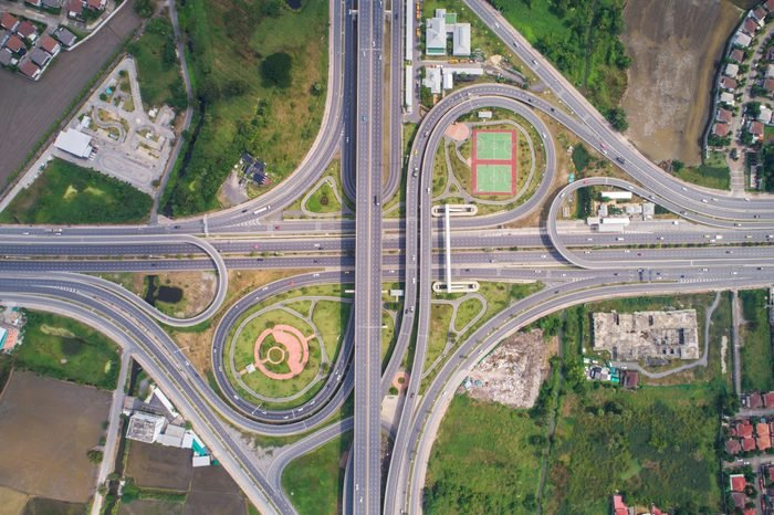 Intersection traffic circle road with car and green tree look down view