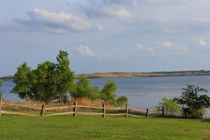 A shot of Kanopolis Lake on the north side of a Wooden Fence, green grass,water,trees, blue sky and clouds, thats bright and colorful.