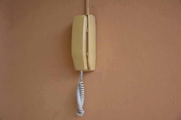 Old office phone on the orange wall