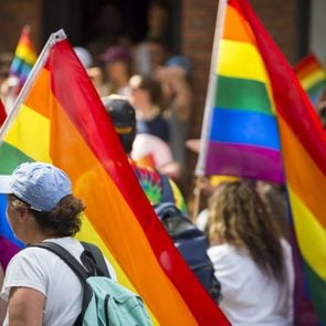People with rainbows flags in the annual Pride Parade as it passes through Greenwich Village.