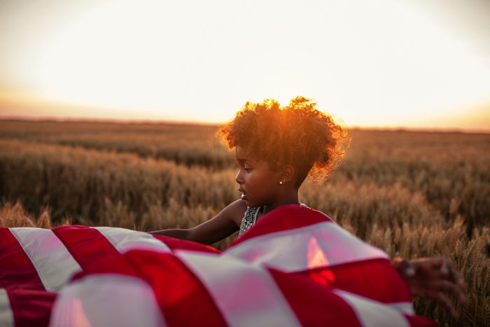 Photo of a beautiful african american girl holding an american flag in the wheat field at sunset.