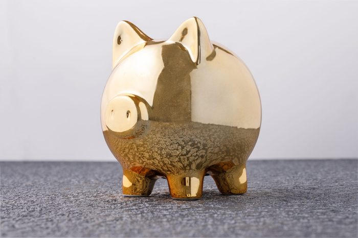 Pig money box golden on black background concept of financial insurance, protection, safe investment or banking. Close-up.