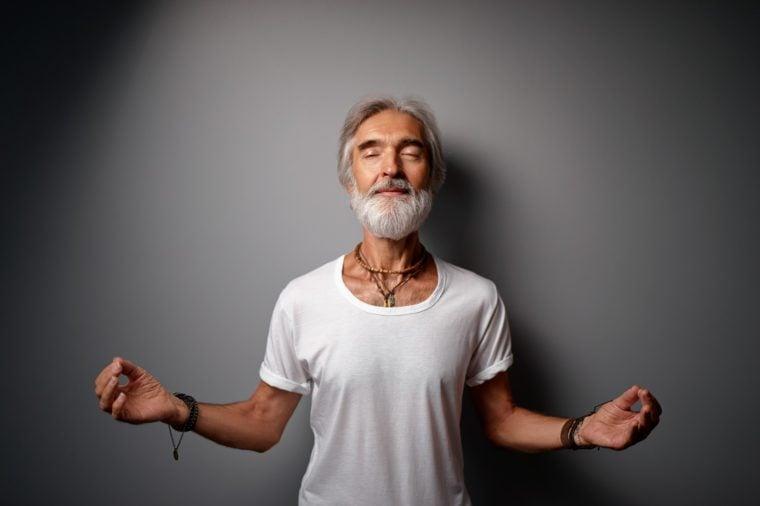 Studio portrait of senior bearded man in lotus pose. Concept of calm and meditation.