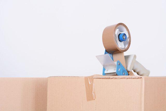 Tape dispenser sealing a shipping cardboard box. Indoors