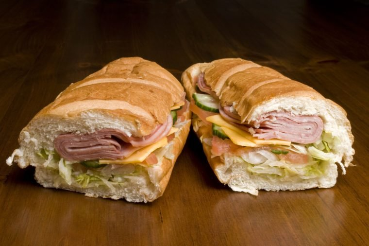 Two halves of a submarine sandwich filled with meat, cheese, cucumber, and lettuce.