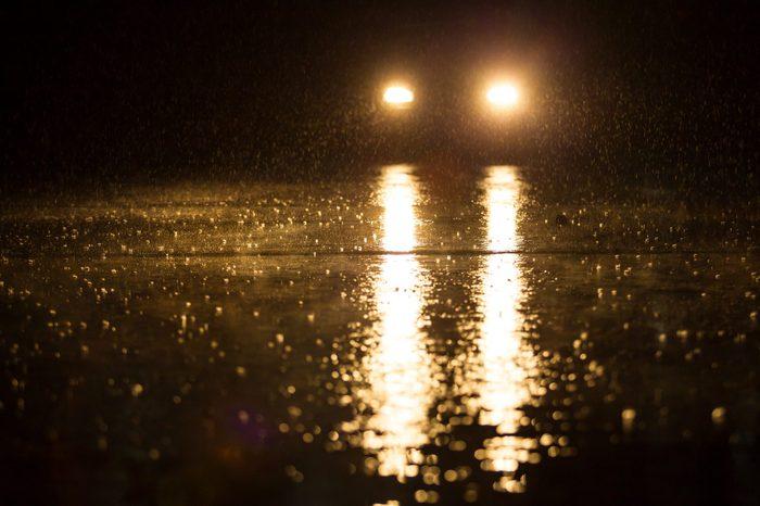 Yellow headlight and road in the dark while heavy raining.