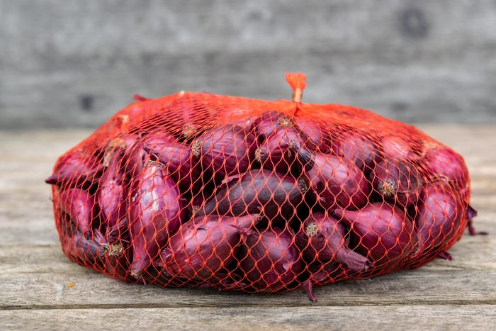 Farming,cultivation, agriculture and vegetables concept: small red onion in a plastic netting bags,prepared for planting in the garden on a wooden table.