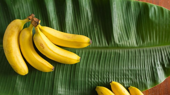 a pile of yellow bananas lay on top of the green fresh banana leaf
