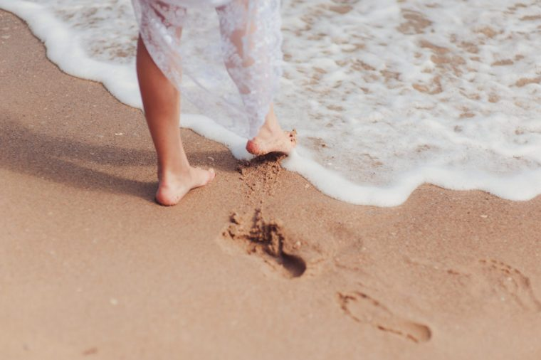 Cropped photo of feet of bride in white lace wedding dress on clean beach. Female legs on sandy beach and waves of sea or ocean, summer vacation at water. Wedding, rest, relax concept.