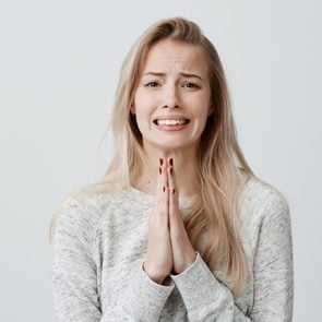 Beautiful blonde female clenching teeth with begging look holding palms pressed together in front of her, asking for forgiveness, feeling sorry after she hurt her boyfriend's feelings. Body language