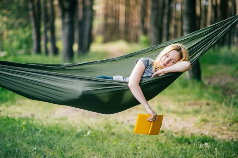 Outdoor portrait of young beautiful blonde girl sleeping in hammock in forest. Pretty woman dreaming at nature in summer. Tired female resting in camping trip after walk. Travel equipment