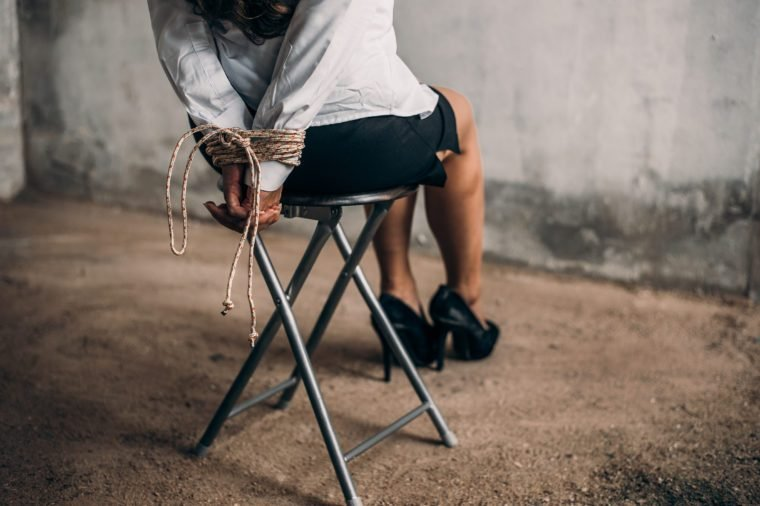 woman hands bound. Women were handcuffed and Sitting on a chair.woman tied hand to a chair.Crime Concept.Criminality Concept.Bonded business.