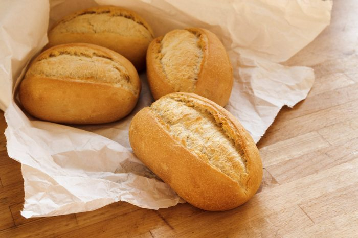 bread rolls or buns for breakfast fresh from the bakery in a white paper bag on a wooden table, selected focus, narrow depth of field