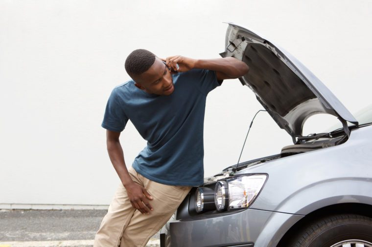 Portrait of young african guy standing near broken car and calling for help on mobile phone