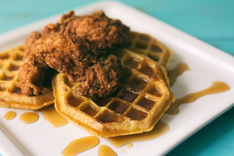 Chicken and waffles with syrup on a white square plate.