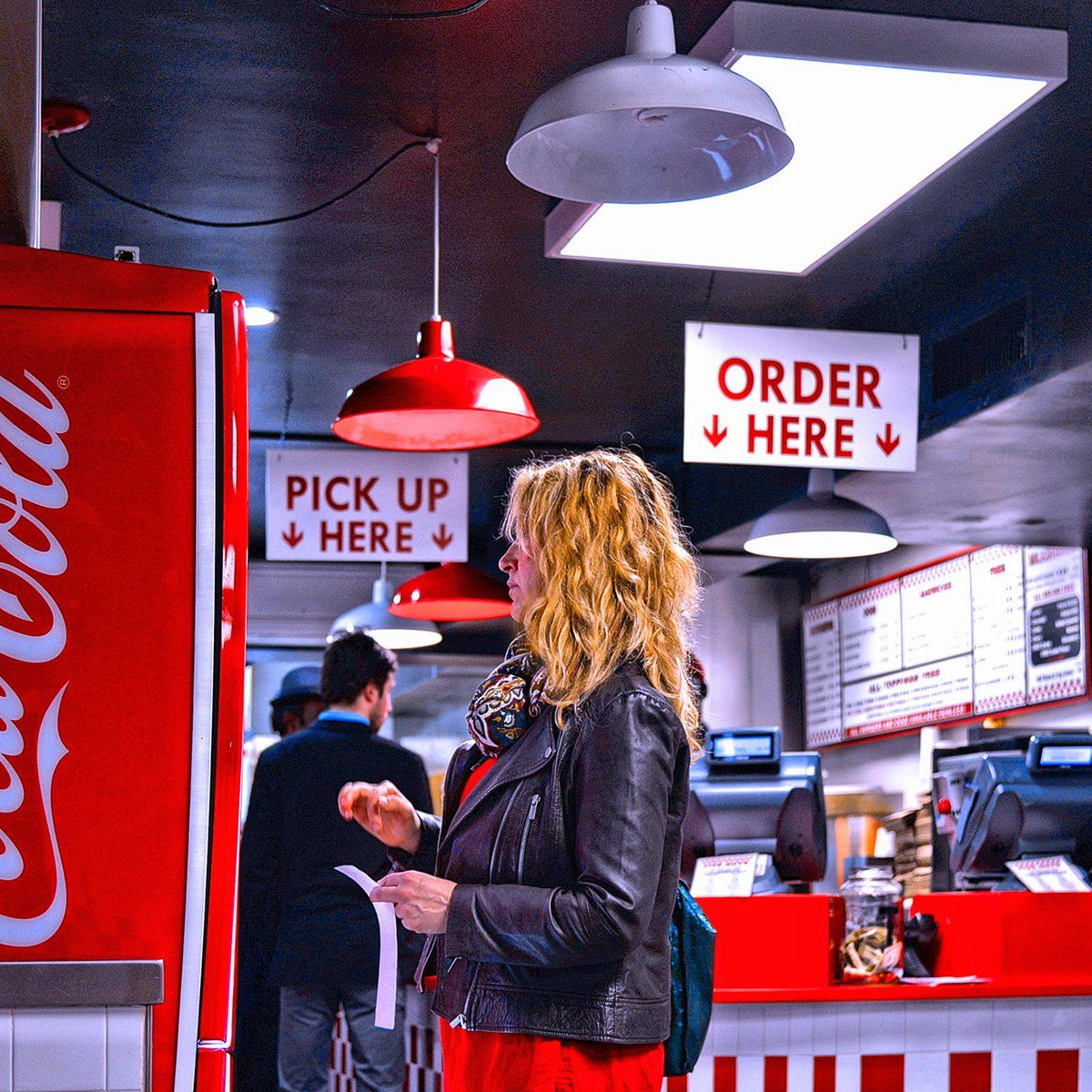 People eating in Five Guys burger fast food restaurant and girl taking a Coca Cola drink