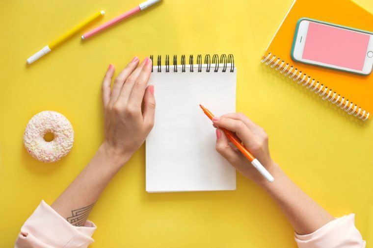 Colorful yellow background with stationary, donut, smart phone mock-up woman's hands writing in empty notebook. Flat lay top view. Learning to draw, making wish list or plans. Art education concept