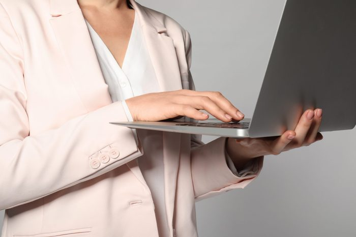 Female manager with laptop on grey background, closeup