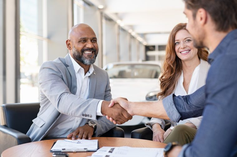 Smiling couple buying a new auto at car showroom. African salesman making handshake with young man purchasing new car with his girlfriend. Happy african agent shaking hands with customer couple.