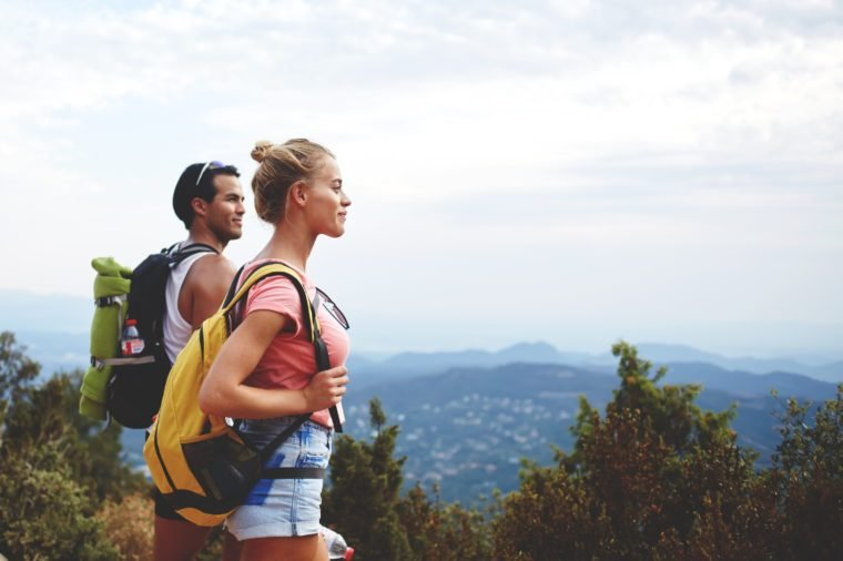 Young man and woman travelers are enjoying amazing nature view during their backpacking, two hikers with rucksacks are resting after active walking in mountains during their summer weekend overseas