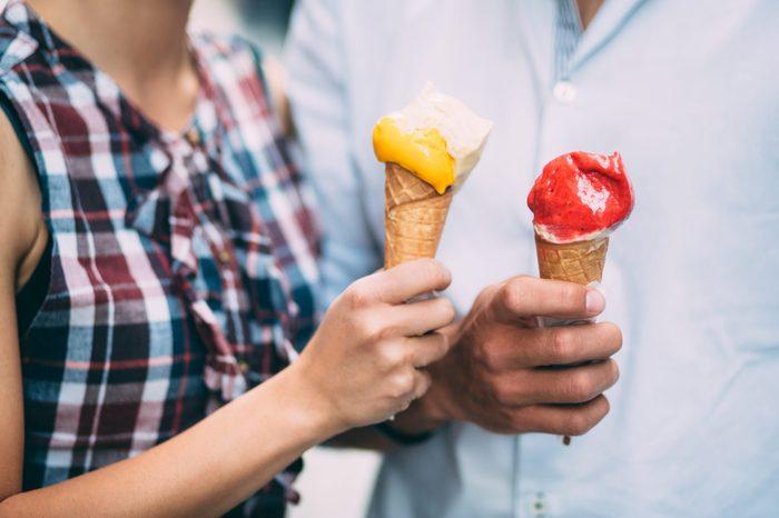 Couple eating ice cream on street