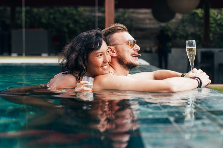 Couple has a rest in the pool with champagne and a cigar