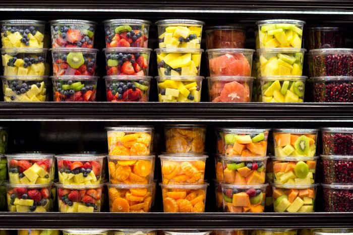 Assortment of cut fruit in containers on display for sale