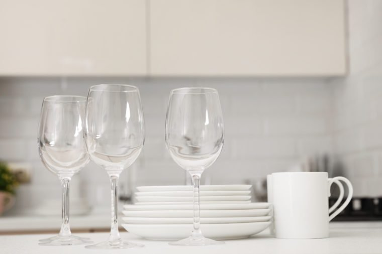 Stack of clean dishes, glasses and cups on table in kitchen