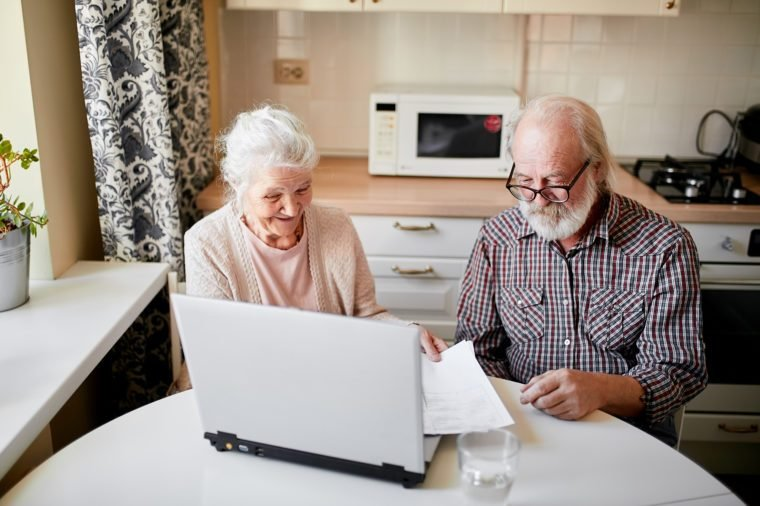 Elderly couple hold papers using laptop for online banking in cozy kitchen, satisfied senior couple smiling while browsing their family photos on digital gadget. Age, users and technology concept
