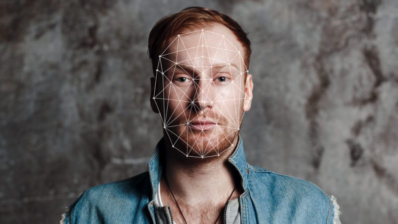 Facial recognition security system. Face augment mobile phone technology concept. Young male looking to camera with authentication grid on his face.