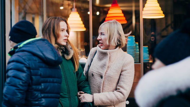 Beautiful mature mother and her adult daughter are talking, smiling, walking together outdoor in winter city street. Bonding, different generationsconnect, family concept.