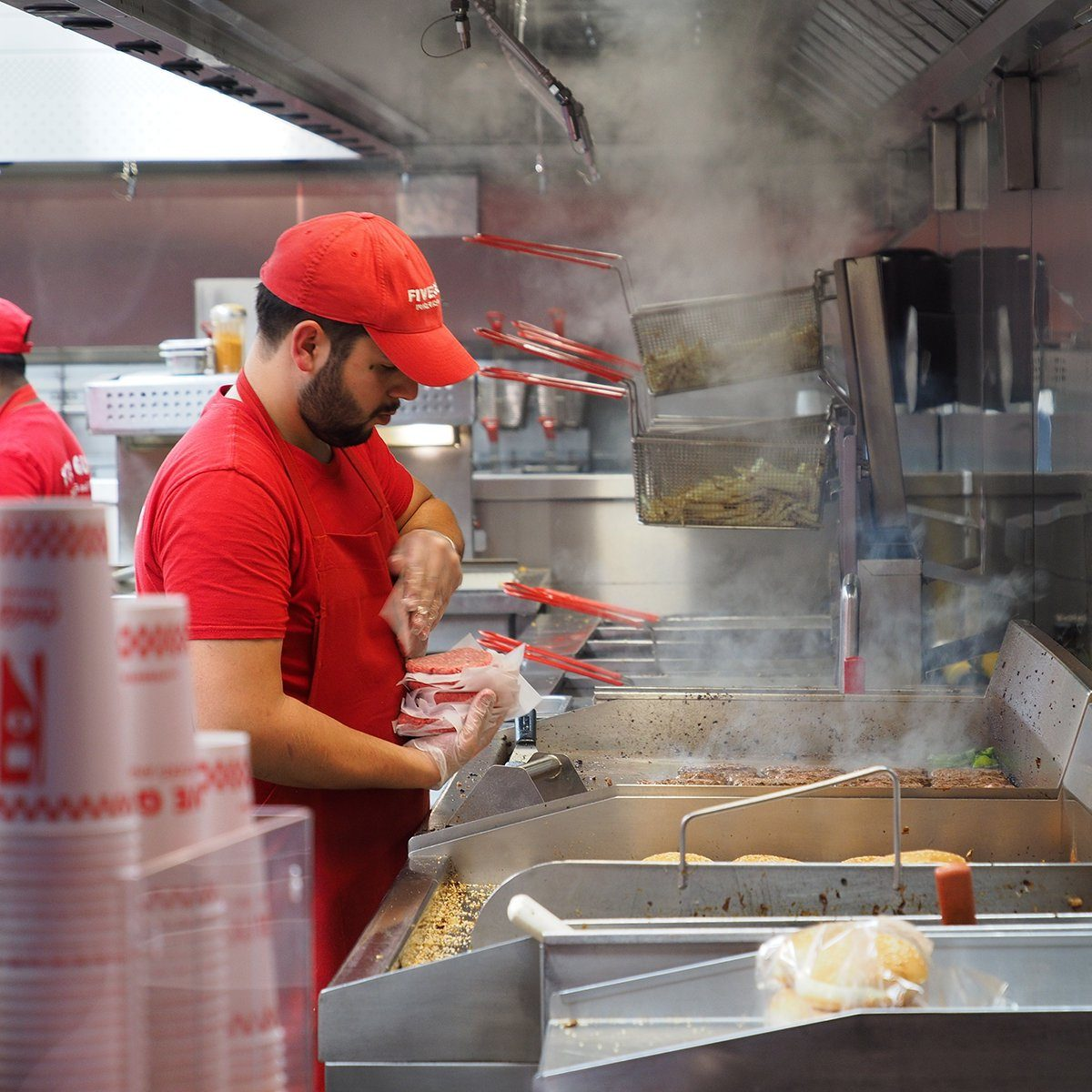 Closeup of crews working at Five Guys burger chain busily, Avenue des Champs