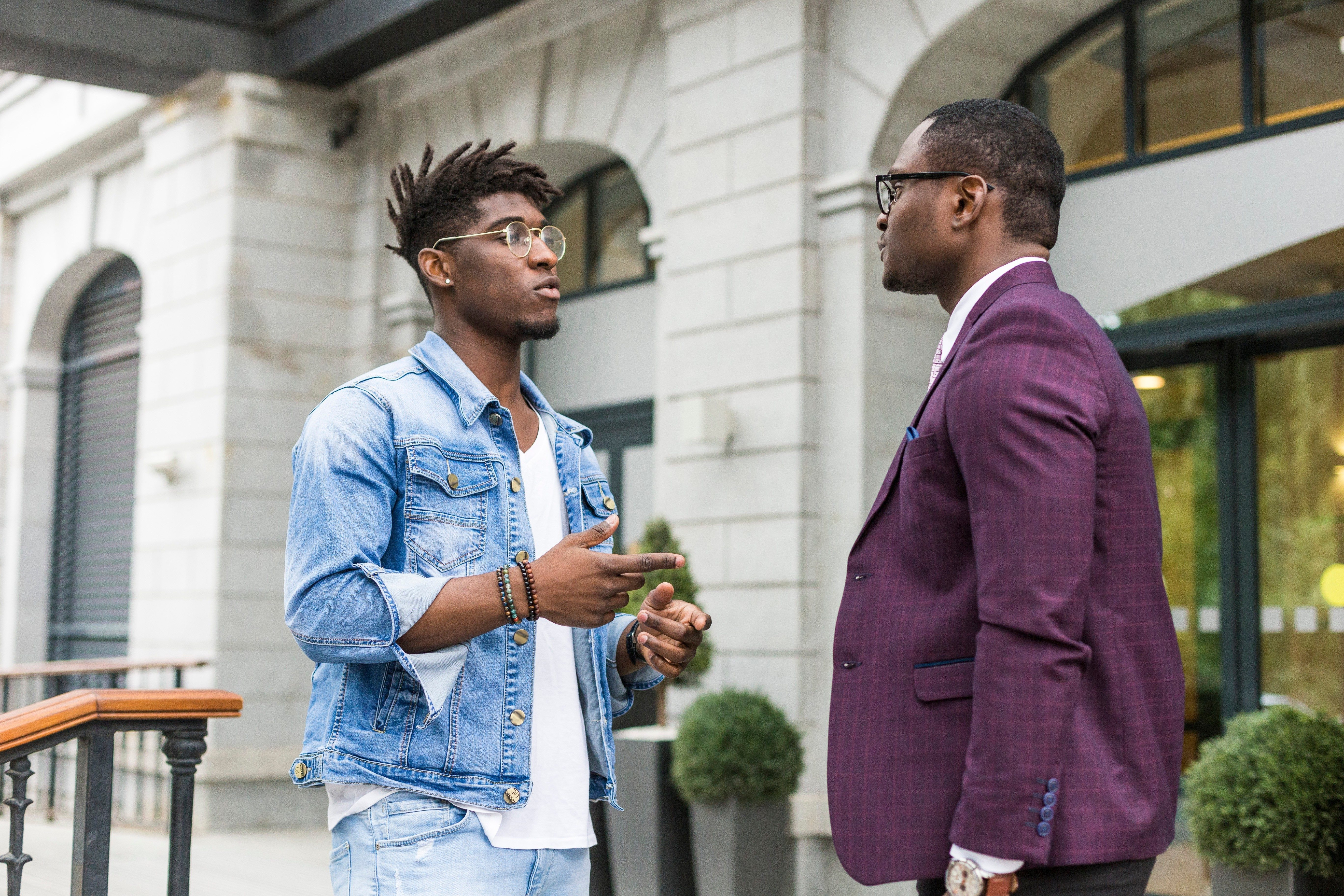 two young and stylish African American men in the city smiling and talking. father and adult son relationship