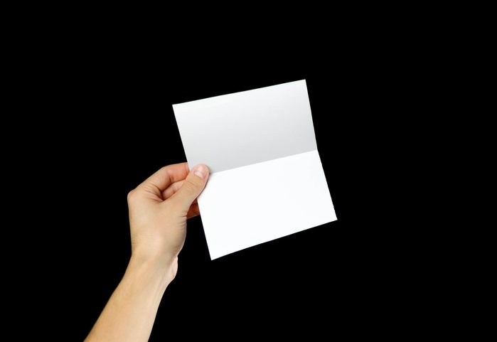 Hand holding blank brochure booklet in the hand. Isolated on black background. Man show offset paper. Sheet template. Book in hands. Booklet folding design. Fold paper sheet display read.