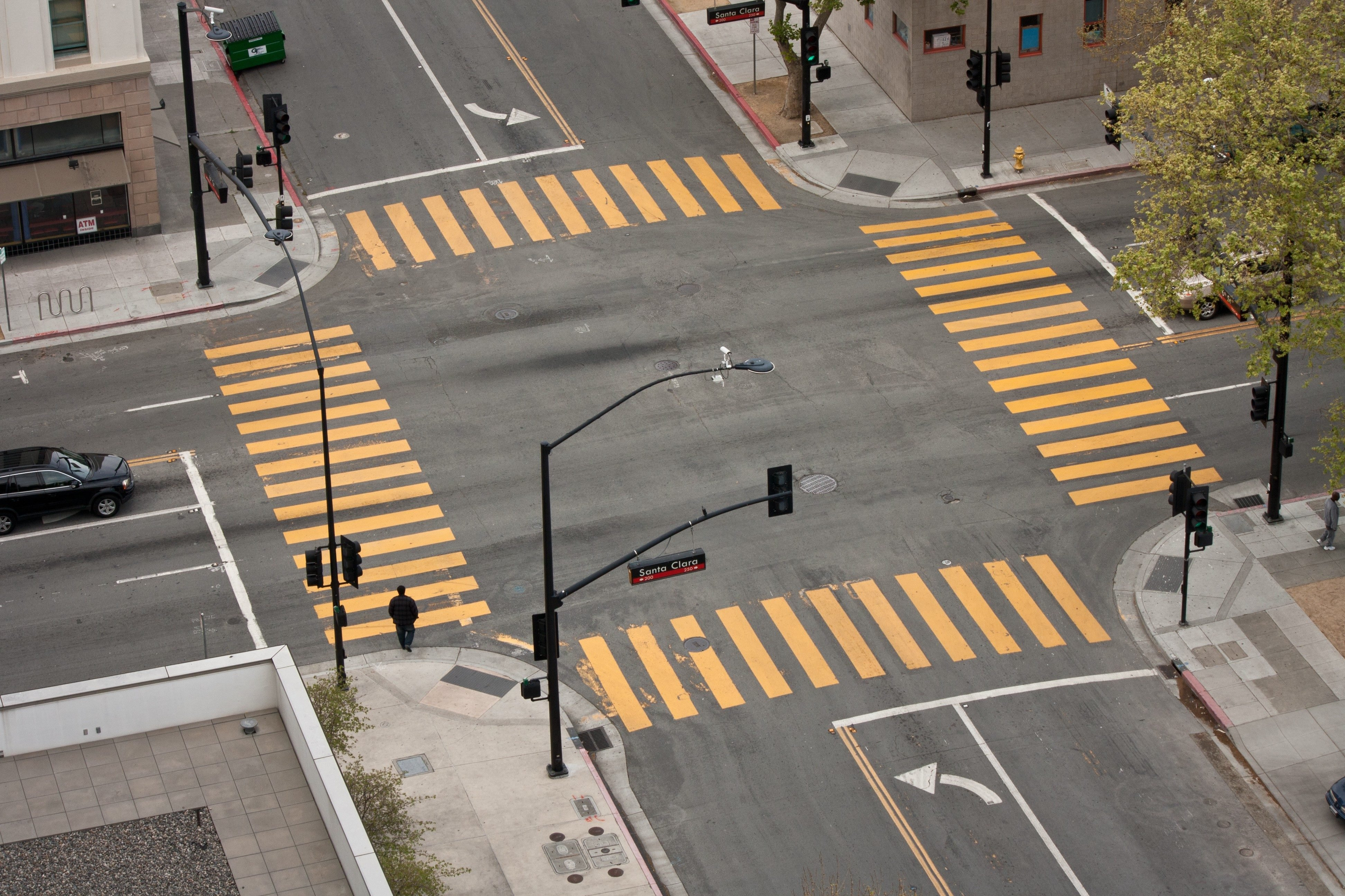 A high angle view of an almost empty street intersection, with yellow cross walk markings, traffic signal lights, and curb cuts, in San Jose, California.