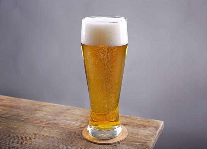 Glass of light beer on grey background