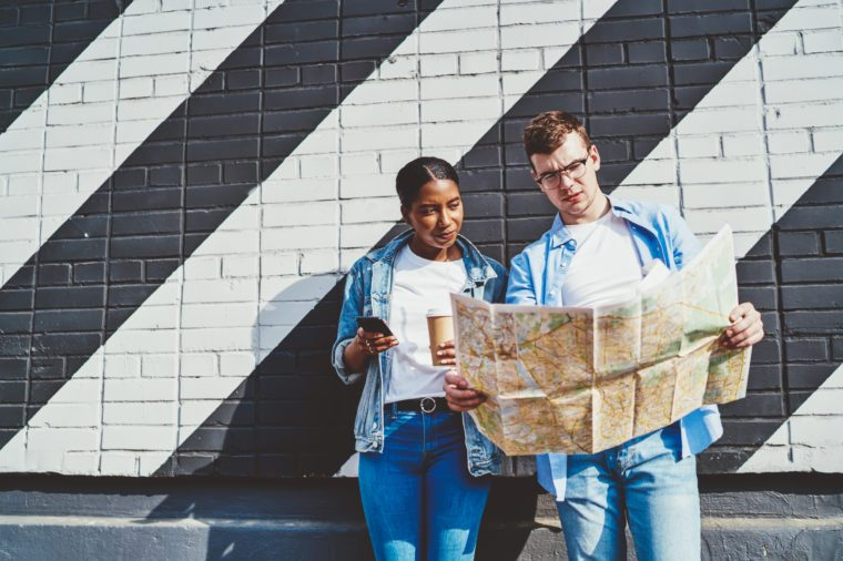 Caucasian young man together with African American hipster girl reading travel map to search right route during trip standing near copy space wall. Diverse couple millennial of tourists sightseeing