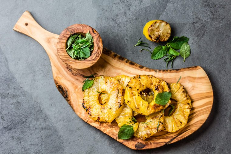 Grilled pineapple slices with mint on olive wooden board. top view