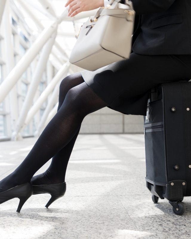 businesswoman sitting on carry bag
