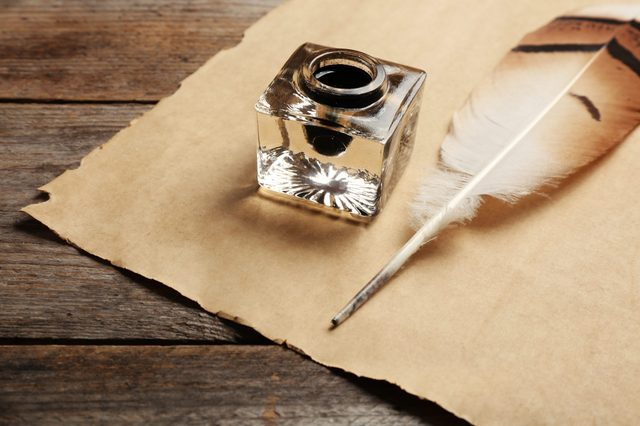 Feather pen, inkwell and blank parchment on wooden table